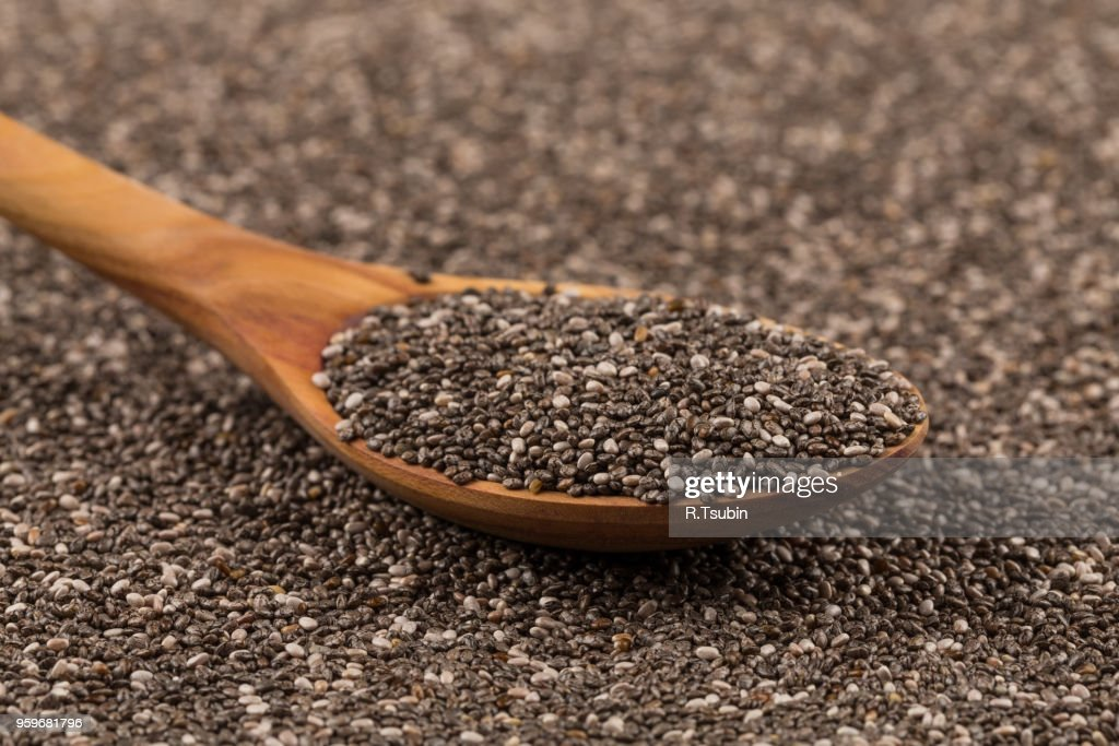 Chia seeds in a wooden spoon on chia background : Stock-Foto