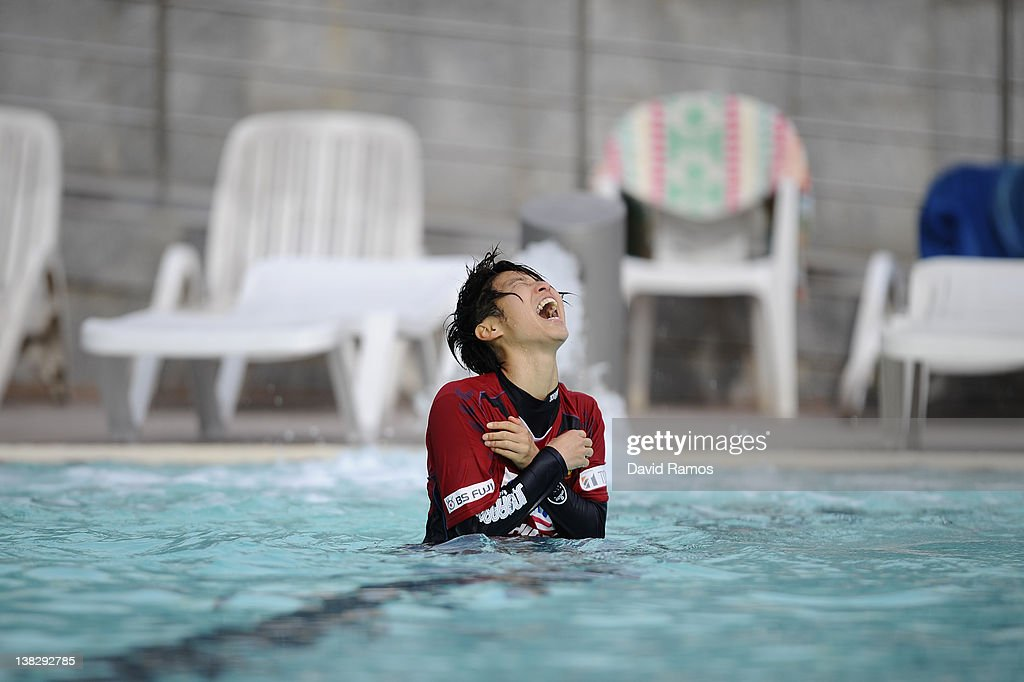 Chiaki Minamiyama of INAC Kobe Leonessa Ladies reacts to the water temperature after being thrown into an outdoor swimming pool by her teammates, foloowing a session at the Club Natacion Barcelona sport complex in La Barceloneta beach on February 5, 2012 in Barcelona, Spain.