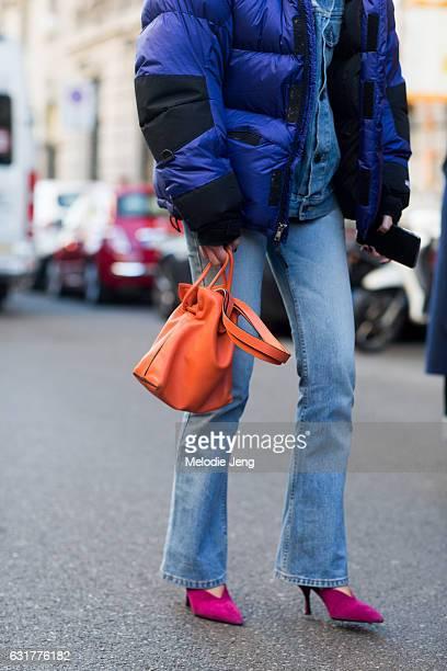 Chiara Capitani wears a blue North Face puffer jacket over a denim jacket flared jeans an orange Loewe bag and pink kitten heels during Milan Men's...