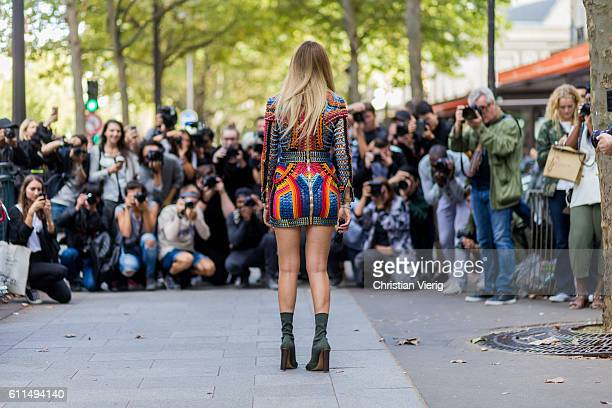 Chiara Ferragni posing in front of street style photographers wearing a Balmain dress and shoes outside Balmain on September 29 2016 in Paris France