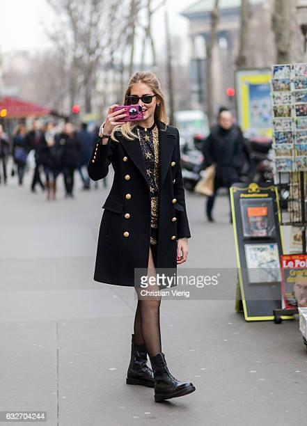 Chiara Ferragni taking photos with her phone in a Chiara Ferragni Collection iphone case wearing a black coat golden dress tights ankle boots outside...