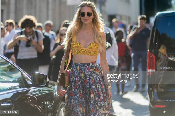 Chiara Ferragni wearing a golden cropped top skirt with floral print and Prada bag is seen outside Prada during Milan Men's Fashion Week...