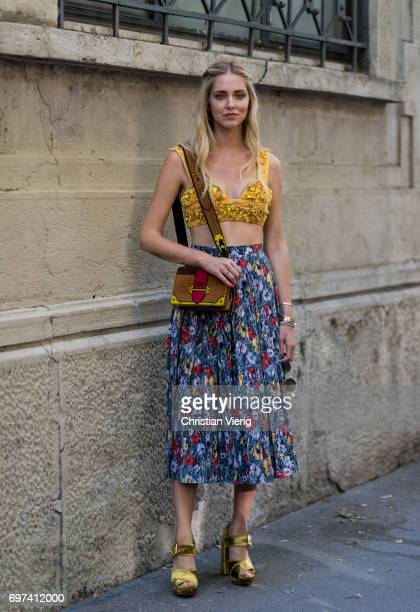 Chiara Ferragni wearing a golden cropped top, skirt with floral print and Prada bag is seen outside Prada during Milan Men's Fashion Week...