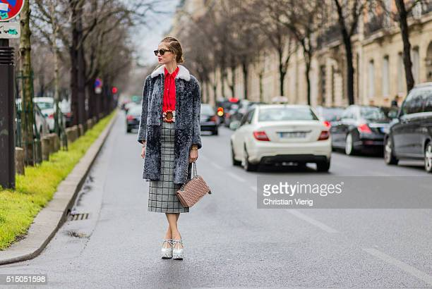 Chiara Ferragni wearing red blouse grey plaid long skirt white heel shoes and a grey fur coat and bag from Miu Miu outside Miu Miu during the Paris...