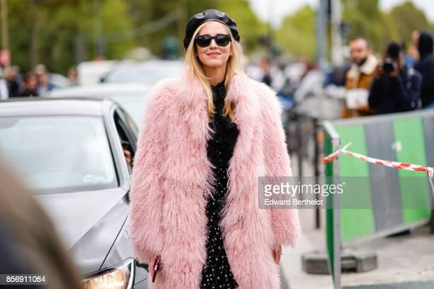 Chiara Ferragni wears a beret hat sunglasses a pink fur coat a black dress chanel slinback shoes outside Giambattista Valli during Paris Fashion Week...