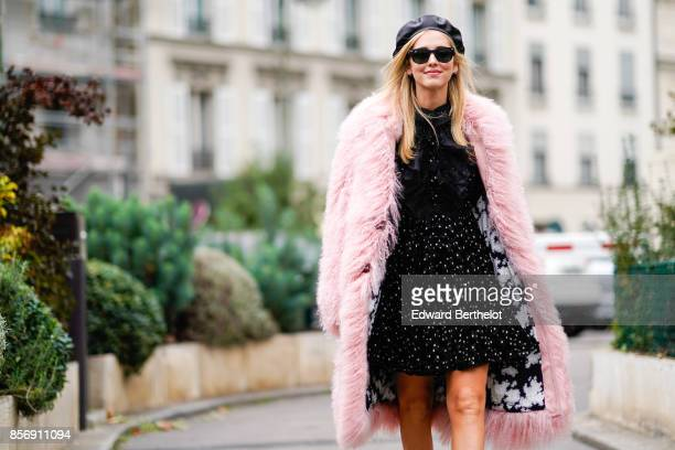 Chiara Ferragni wears a beret hat sunglasses a pink fur coat a black dress chanel slinback shoes outside Giambattista Valli during Paris Fashion Week...