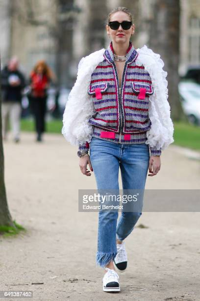 Chiara Ferragni wears a striped tweed colored jacket with white fur sleeves sunglasses blue denim jeans and black and white sneakers outside the...