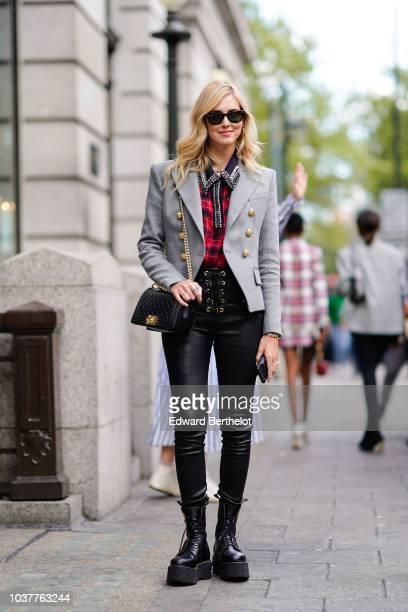 Chiara Ferragni wears sunglasses a gray blazer jacket a red tartan checked shirt black leather pants a Chanel Boy bag black boots during London...