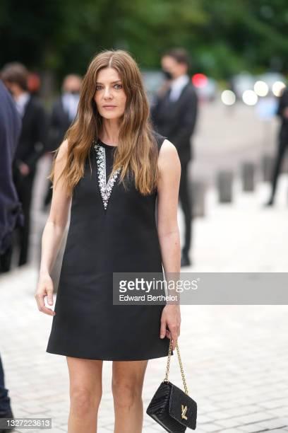 Chiara Mastroianni wears a black sleeveless short dress with a V-neck diamonds from Louis Vuitton, a black handbag from Louis Vuitton, outside Louis...
