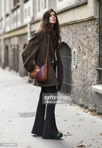 Chiara Totire is seen wearing a brown coat, brown bag and black bellbottom pants outside the Ann Demeulemeester show during Paris Fashion Week S/S...