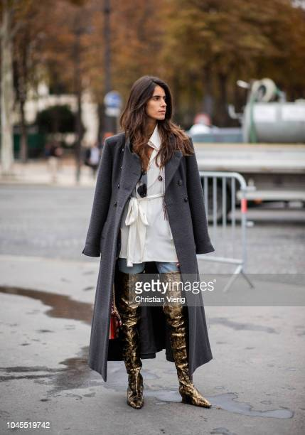 Chiara Totire wearing golden overknees boot black wool coat denim jeans button up shirt is seen outside Chanel during Paris Fashion Week Womenswear...