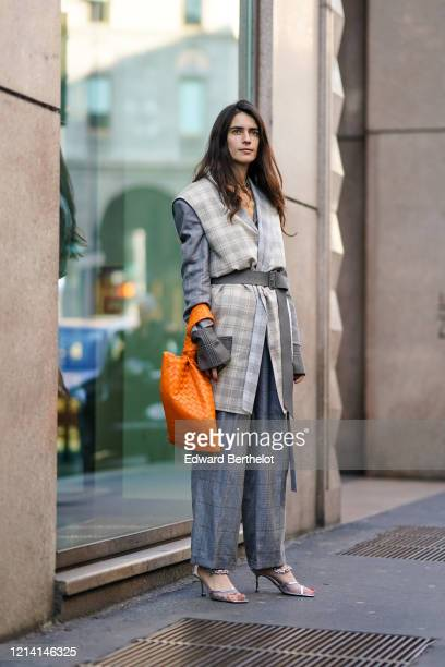 Chiara Totire wears a blue-grey checkered pantsuit with cuffed pants, a light grey checkered sleeveless chasuble, a grey belt, an orange woven...