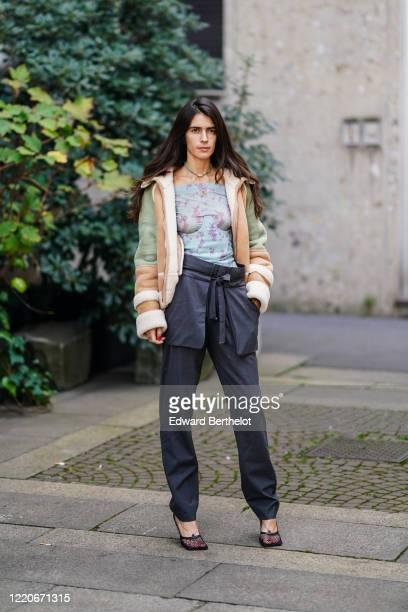 Chiara Totire wears a pale blue top, a green and brown leather aviator jacket, black pants, mesh shoes, outside Koche x Pucci, during Milan Fashion...