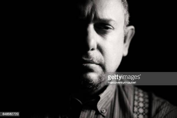 chiaroscuro portrait of a mean looking man - half full stock photos and pictures
