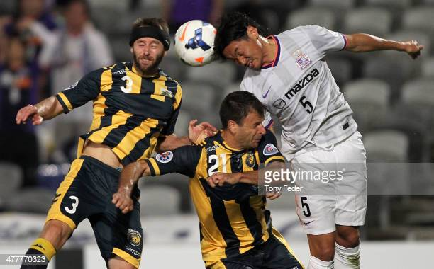 Chiba Kazuhiko of Hiroshima contests a header with Joshua Rose and Mile Sterjovski of the Mariners during the AFC Asian Champions League match...