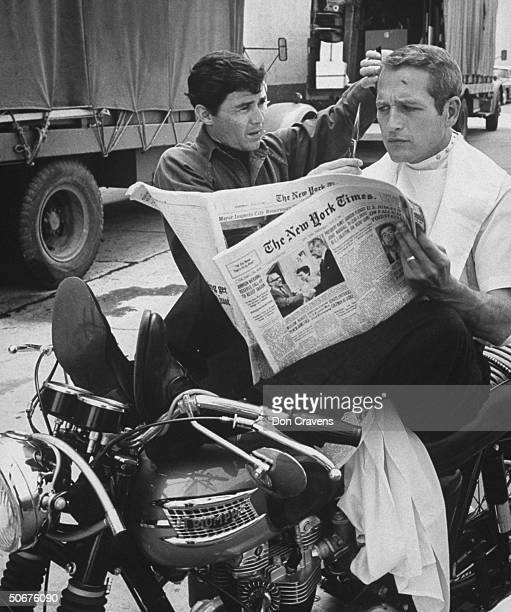 Chic barber Jay Sebring, working on actor Paul Newman's hair while he is reading the paper, sitting on motorcycle on the set of the film Moving...
