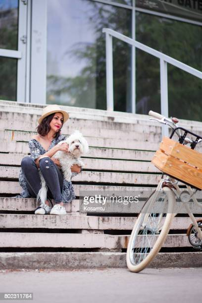 Chic Brunette Girl And Maltese Dog Posing Outdoors In Sunny Springtime