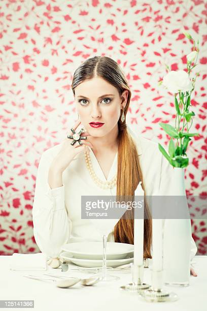 Chic dinner, elegant woman dinning in a white atmosphere.