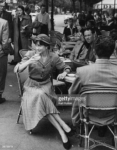 A chic Parisienne sips an aperitif outside a cafe in Paris She is wearing a lowpriced massproduced yet fashionable British dress designed by Norman...