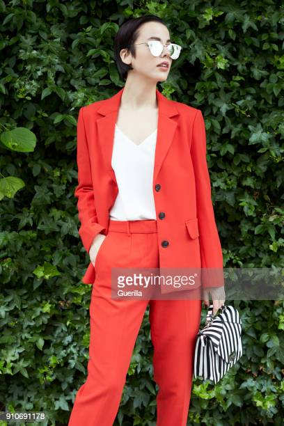 chic woman in red suit in front of foliage looking away - red suit stock pictures, royalty-free photos & images