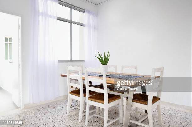 chic wood dining table in a bright dining room - dining room stock pictures, royalty-free photos & images
