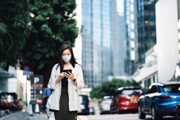 Chic young Asian businesswoman with protective face mask using mobile app device on smartphone to order taxi pick up service by the urban road in downtown city street. Speedy and trustworthy service. Carsharing and business on the go themes