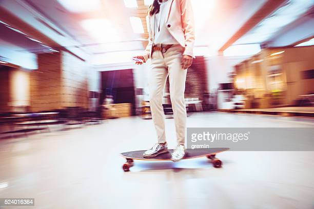 Chic young businesswoman skateboarding in offices