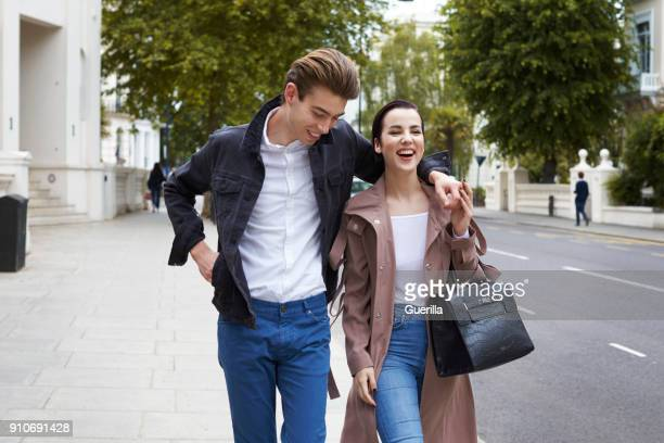 chic young couple walking in the street in notting hill gate - オールバック ストックフォトと画像