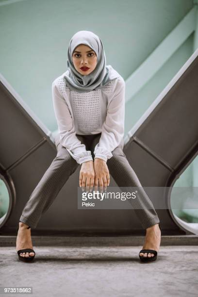 chic young muslim girl sitting comfortably in modern scene - malaysia beautiful girl stock photos and pictures