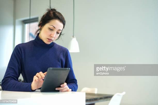 Chica en la cocina navegando con su tablet