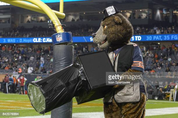 Chicago Bears mascot Staley carries a camera while wearing a photographer's vest and a hat that says fake news during an NFL preseason football game...