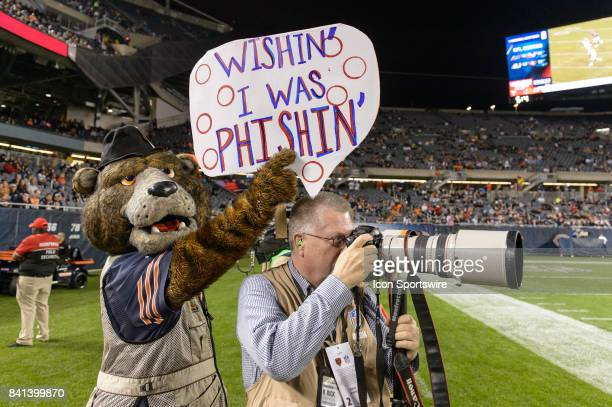 Chicago Bears mascot Staley holds a sign above photographer H Rick Bamann during an NFL preseason football game between the Cleveland Browns and the...