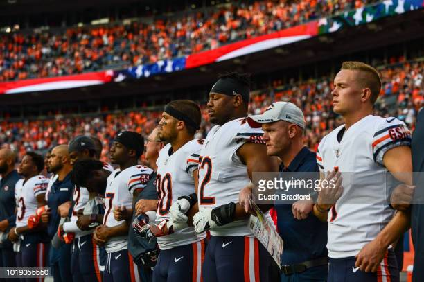 Chicago Bears players stand with arms locked during the performance of the national anthem before an NFL preseason game against the Denver Broncos at...