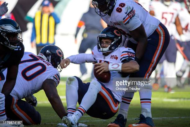 Chicago Bears quarterback Mitch Trubisky is helped up by Chicago Bears offensive guard James Daniels after being sacked during the second quarter by...