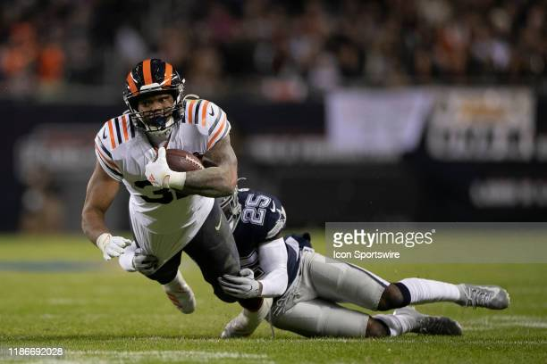 Chicago Bears running back David Montgomery battles with Dallas Cowboys free safety Xavier Woods in game action during a NFL game between the Chicago...