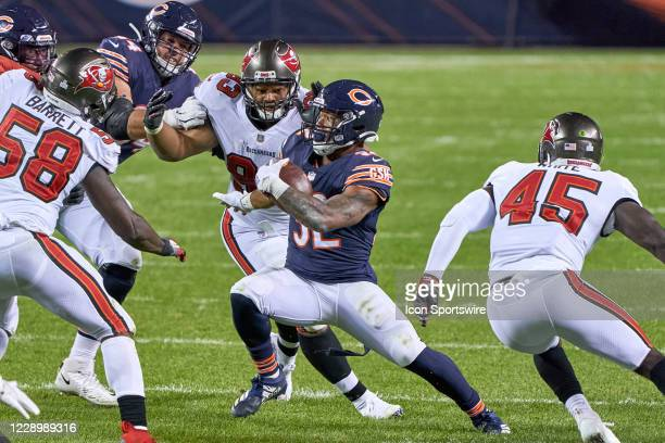Chicago Bears Running Back David Montgomery battles with Tampa Bay Buccaneers Defensive End Ndamukong Suh and Linebacker Devin White in game action...