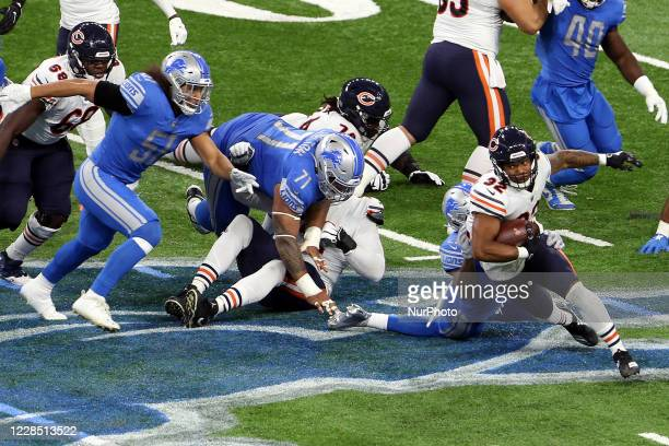 Chicago Bears running back David Montgomery runs the ball under the pressure of Detroit Lions defense during the first half of an NFL football game...