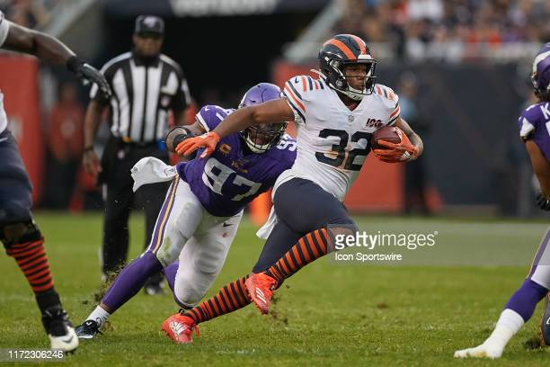 Chicago Bears running back David Montgomery runs with the football past Minnesota Vikings defensive end Everson Griffen in game action during a game...