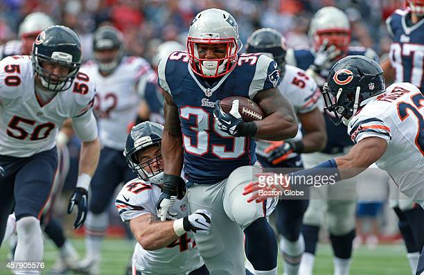 Chicago Bears safety Chris Conte hangs on as he d=tries to drag down New England Patriots running back Jonas Gray but not before Gray picked up a...