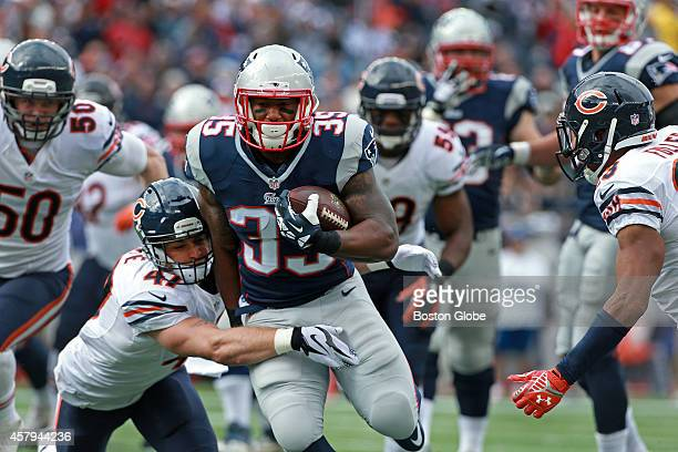 Chicago Bears safety Chris Conte hangs on as he tries to drag down New England Patriots running back Jonas Gray but not before Gray picked up a...