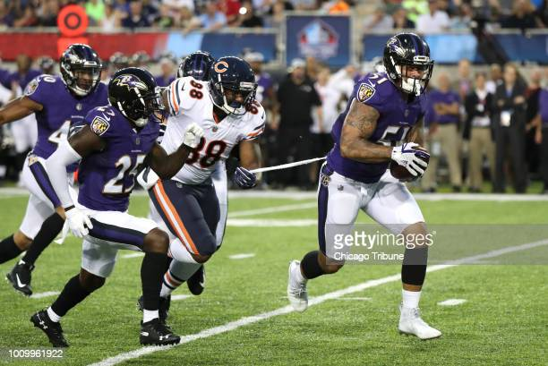 Chicago Bears tight end Dion Sims grabs a bit of fabric as he tries to tackle Baltimore Ravens linebacker Kamalei Correa after Correa intercepted a...