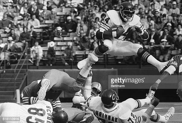 Chicago Bears' Walter Payton hurdles over fallen teammate Gary Hrivnak as he returns the kickoff in the first quarter Payton took the kickoff two...