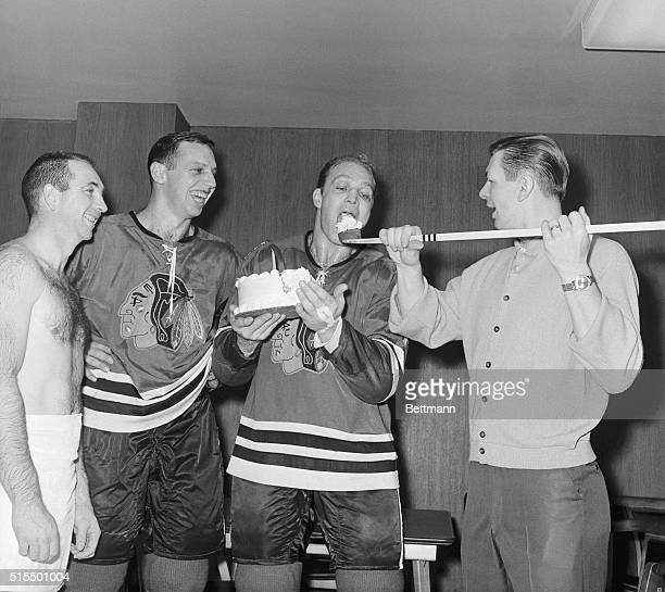Chicago Black Hawks' Stan Mikita uses a hockey stick to serve up a piece of birthday cake to teammate Bobby Hull during a small celebration for...