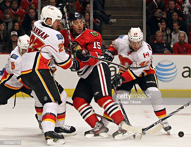 Chicago Blackhawks' Andrew Brunette is kept from the puck by Calgary Flames' Scott Hannan and Alex Tanguay in the third period at the United Center...