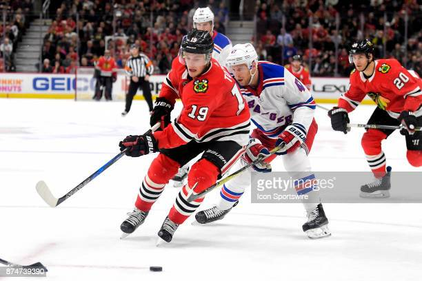 Chicago Blackhawks center Jonathan Toews battles with New York Rangers defenseman Steven Kampfer for a loose puck in the third period during a game...