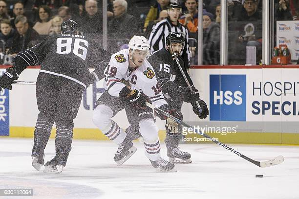 Chicago Blackhawks Center Jonathan Toews makes pass as New York Islanders Winger Nikolay Kulemin and New York Islanders Right Wing Cal Clutterbuck...