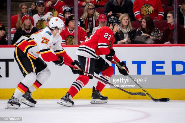 Chicago Blackhawks defenseman Brandon Manning controls the puck against Calgary Flames center Sean Monahan during a game between the Calgary Flames...