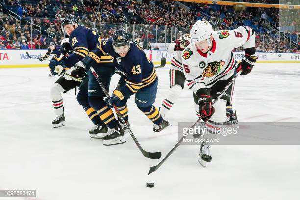Chicago Blackhawks defenseman Connor Murphy and Buffalo Sabres left wing Conor Sheary reach for loose puck as Buffalo Sabres right wing Kyle Okposo...