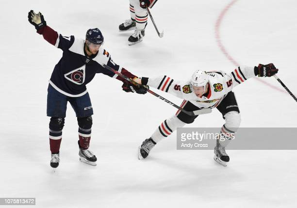 Chicago Blackhawks defenseman Connor Murphy holds onto Colorado Avalanche center Tyson Jost's stick in the second period at the Pepsi Center December...