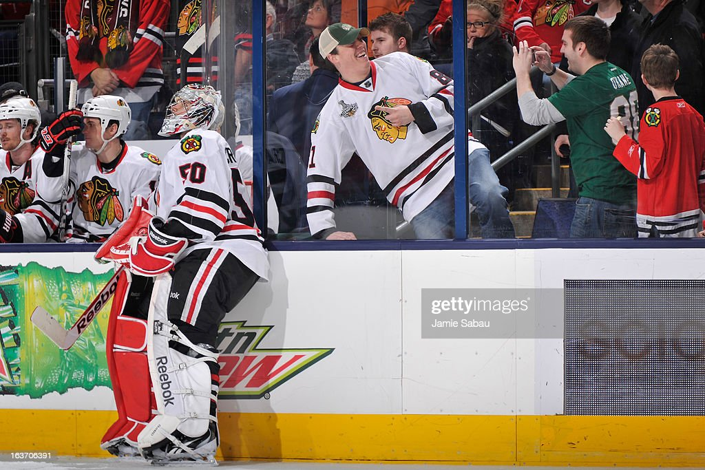 A Chicago Blackhawks fan poses for a picture behind the Chicago bench during the third period on March 14, 2013 at Nationwide Arena in Columbus, Ohio. Chicago defeated Columbus 2-1 in a shootout.